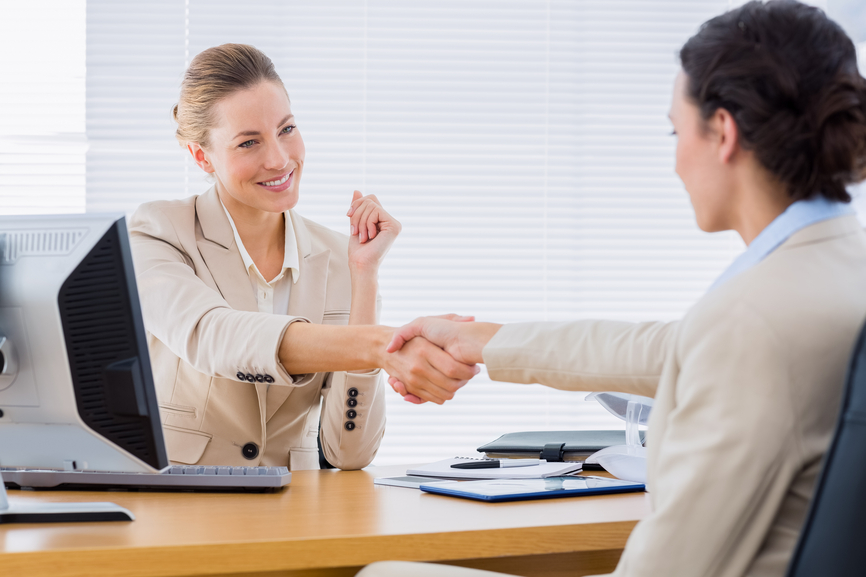 Smartly dressed young women shaking hands in a business meeting at office desk